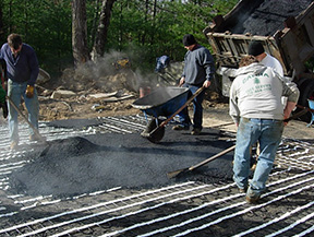 Applying hot asphalt over heat cable mats