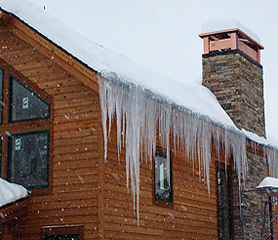 Steep roof with icicles in need of a roof deicing system