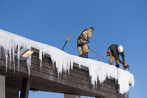 Removing the snow and icicles from a commercial roof.