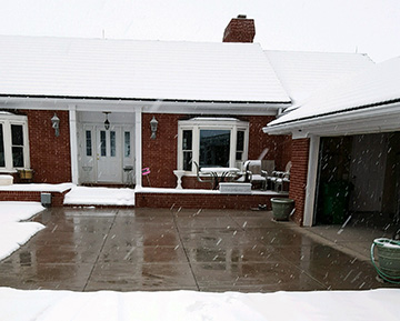 A heated driveway system in concrete operating during a snowstorm.